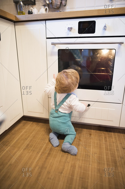 Baby boy sitting in kitchen watching cake baking in oven