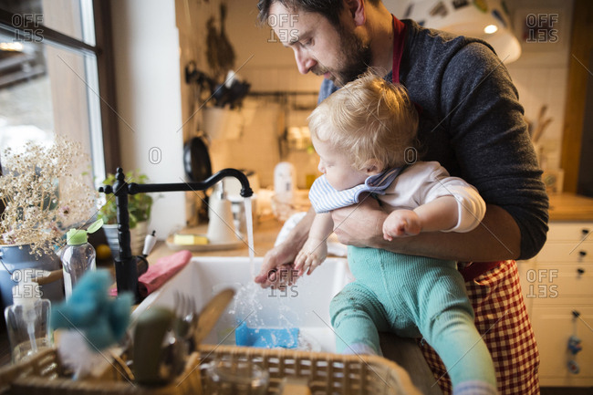 Father and baby boy in kitchen washing dishes