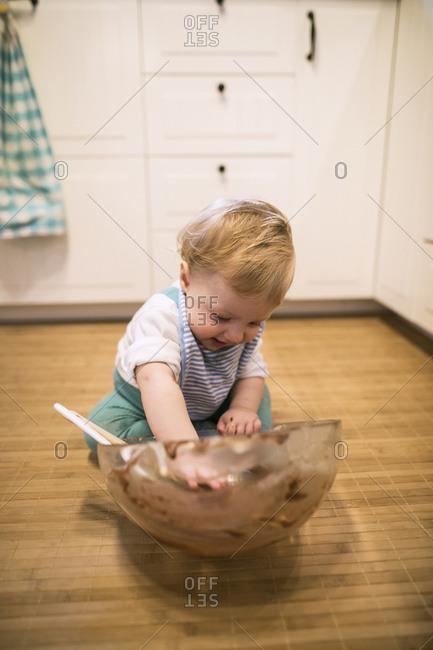 Baby boy sitting in kitchen nibbling cake dough