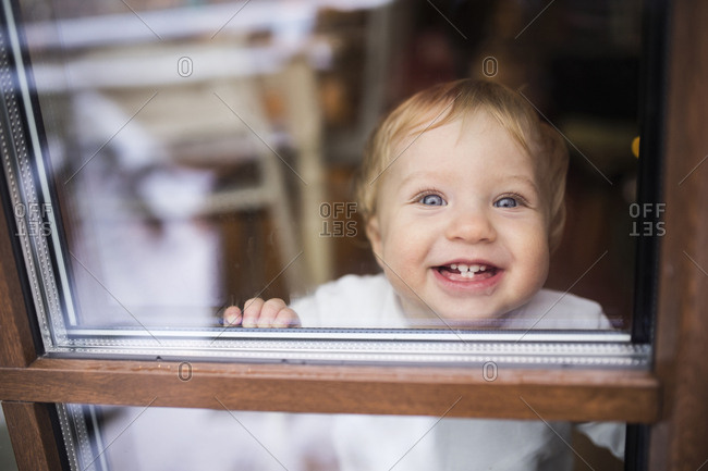 Laughing baby boy looking out of window