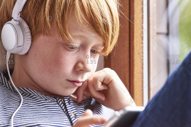 Boy sitting on window sill using digital tablet- wearing head phones