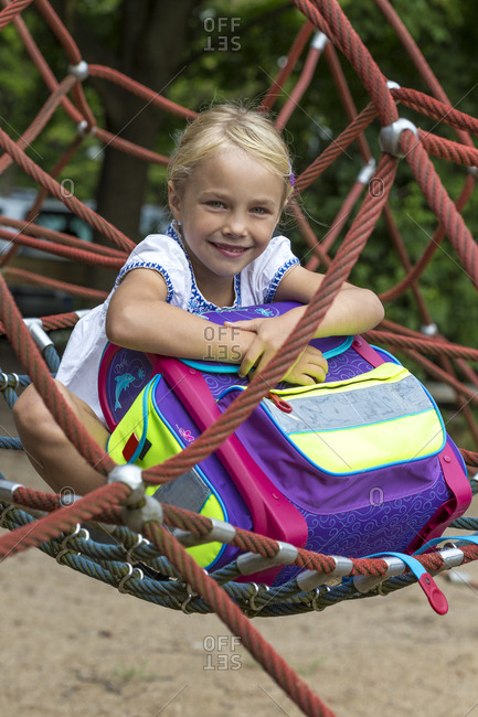 Portrait of smiling little girl with school bag sitting in nest swing on playground