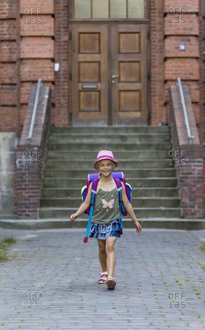 Smiling little girl with school bag in front of her school