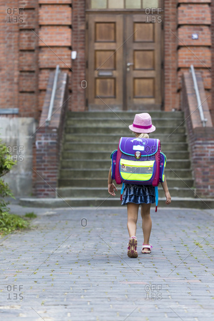 Back view of little girl with school bag in front of her school