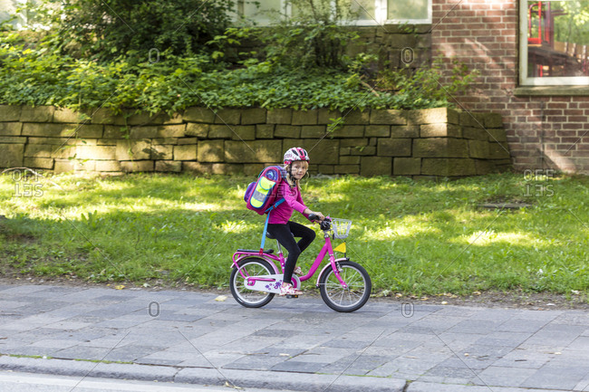 Smiling little girl with school bag riding bicycle on pavement