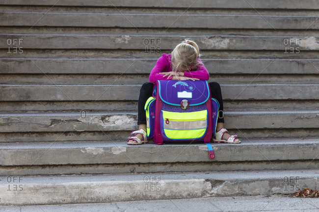 Sad little girl sitting on stairs with school bag