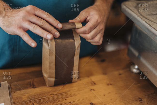 Close-up of man packing bag of coffee at shop counter
