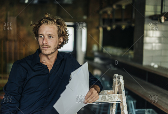 Man leaning on ladder in unfinished room
