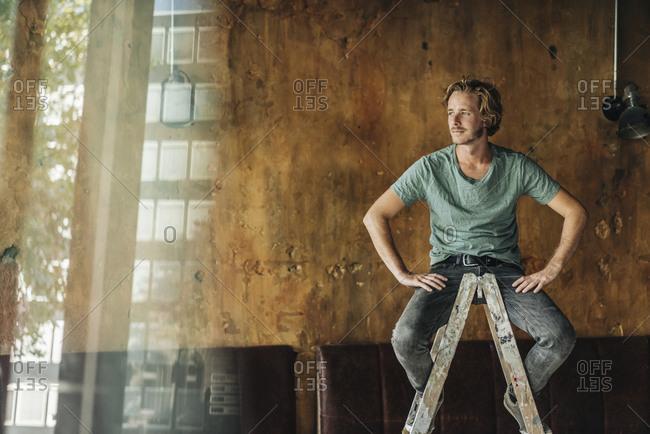 Man sitting on stepladder in unfinished room
