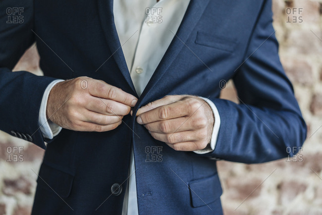 Close-up of of businessman buttoning jacket