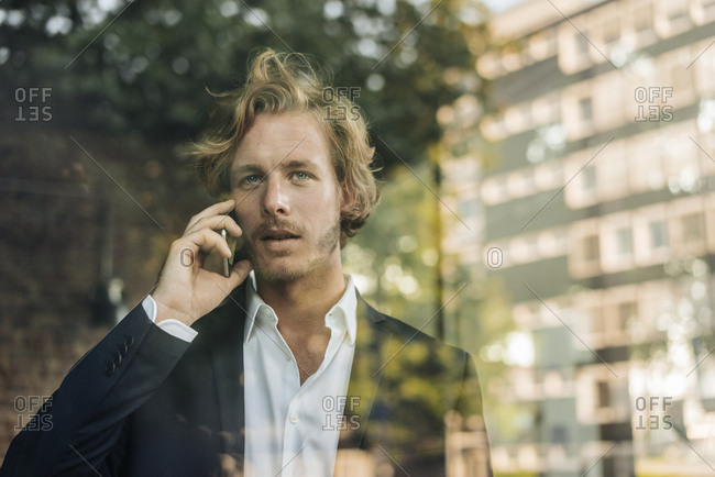 Businessman on cell phone behind windowpane