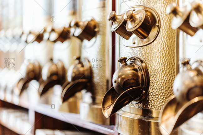 Row of brass coffee dispensers