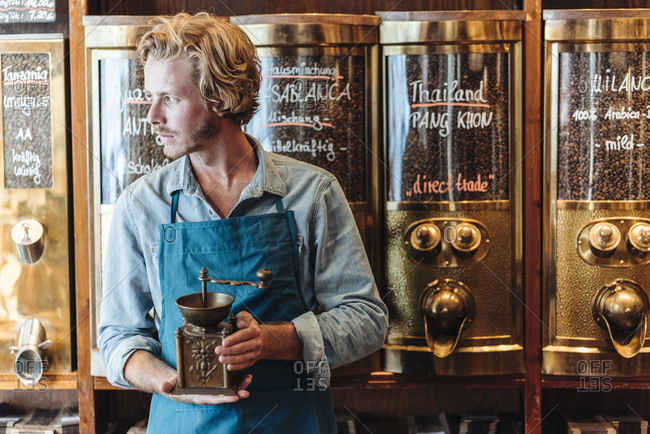 Coffee roaster in his shop holding old-fashioned coffee mill