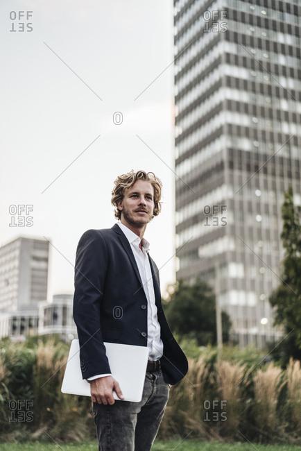 Businessman holding laptop outdoors