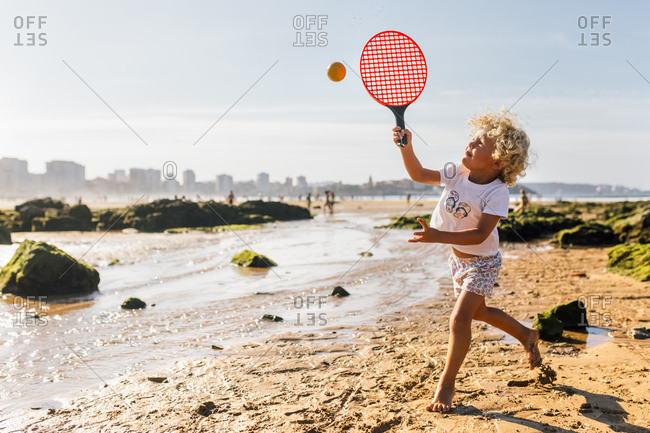 Little boy playing beach paddles on the beach