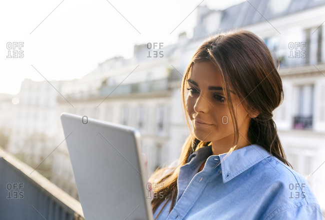Young woman standing on balcony using digital tablet