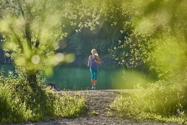 Germany- Bavaria- Young woman jogging at Lake Walchensee