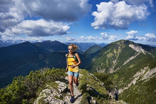 Germany- Bavaria- Young woman running in the mountains
