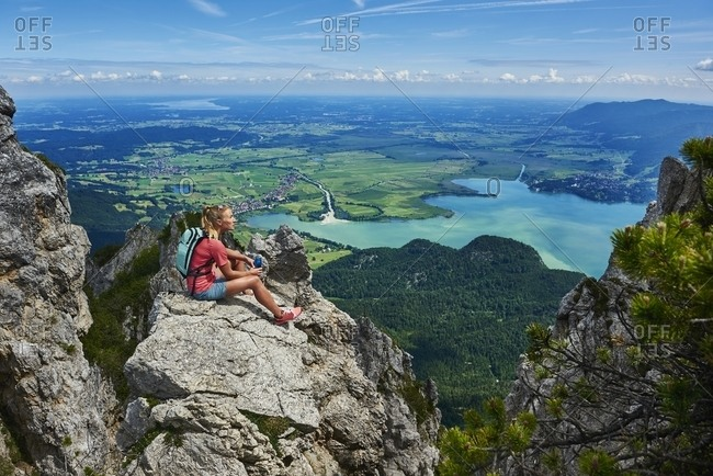 Germany- Bavaria- Young woman taking a break after running in the mountains
