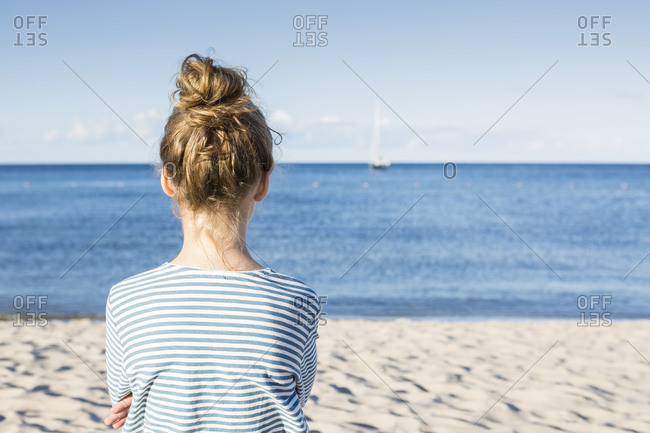 Girl looking at the sea- rear view