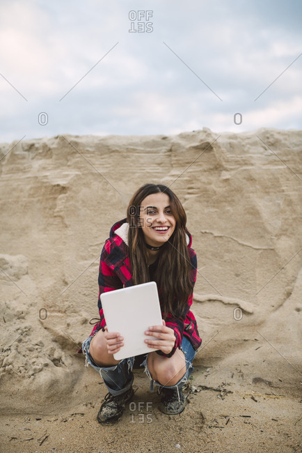 Portrait of smiling young woman with tablet crouching on the beach