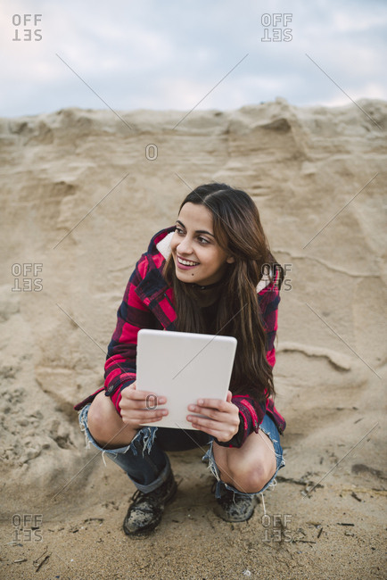 Young woman with tablet crouching on the beach