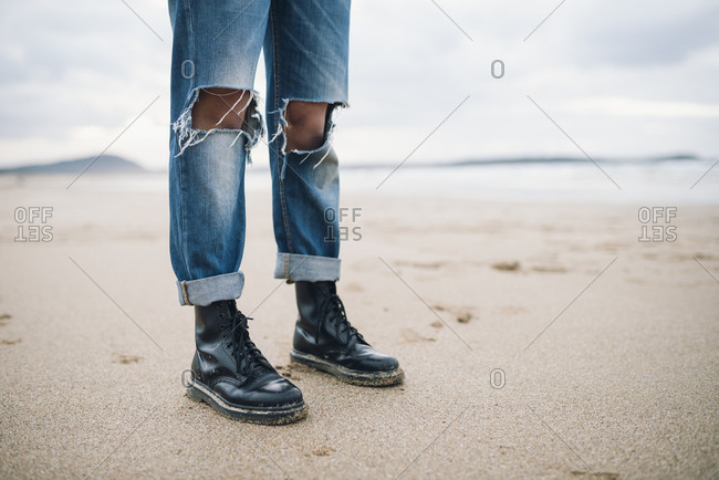 Woman wearing boots and torn jeans  on the beach- partial view