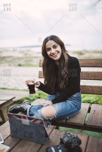 Portrait of smiling young woman with glass of Cola in an outdoor cafe