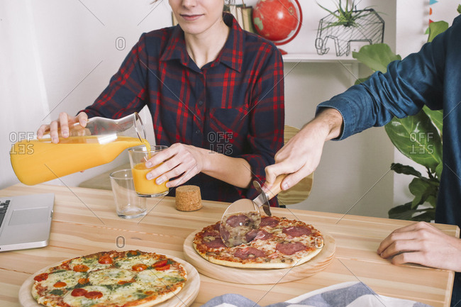 Young couple eating pizza and drinking juice for lunch- laptop standing on table