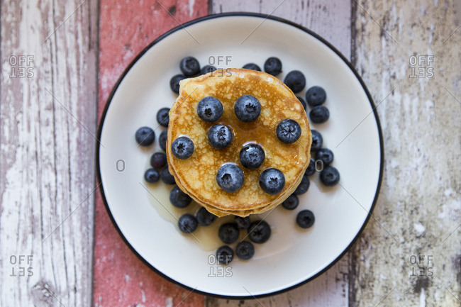 Dish with pile of pancakes and blueberries with maple sirup