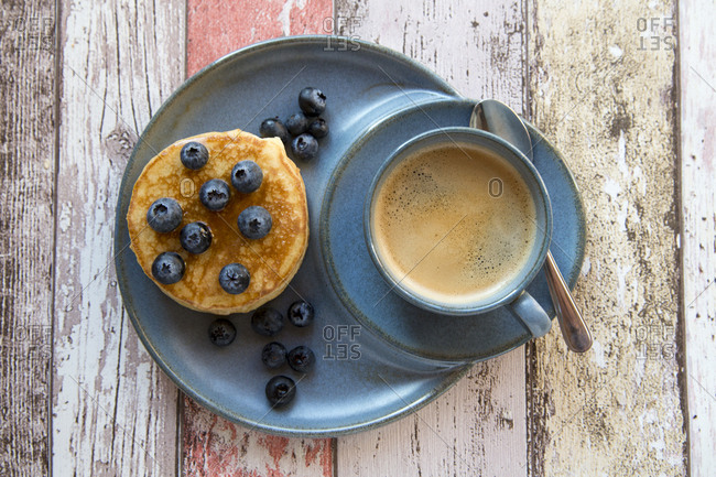 Dish with pancakes- blueberries with maple sirup and a cup of black coffee