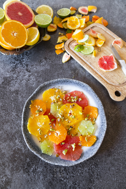 Plate of peeled and sliced citrus fruits with pistachios