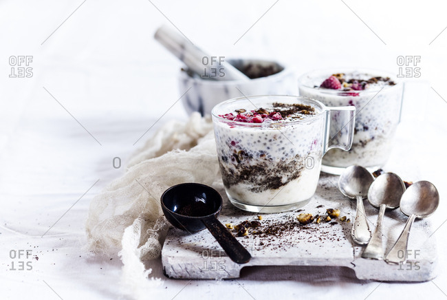 Glasses of yogurt dessert with chia- roasted hazelnuts and coffee