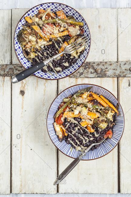 Vegan Buddha bowl of black rice- roasted vegetables- Tahini sauce and sesame seeds