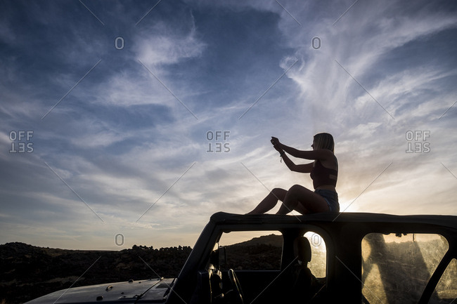 Silhouette of woman sitting on car roof at sunset taking picture