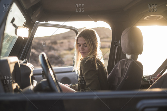 Woman sitting in car at sunset