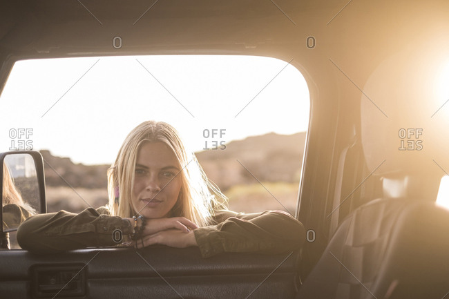 Portrait of young woman leaning on car window looking inside