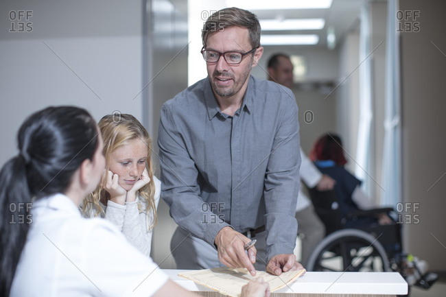 Father and daughter standing at reception in hospital