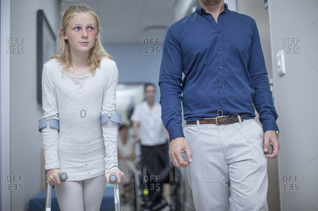 Girl with crutches walking with father in hospital