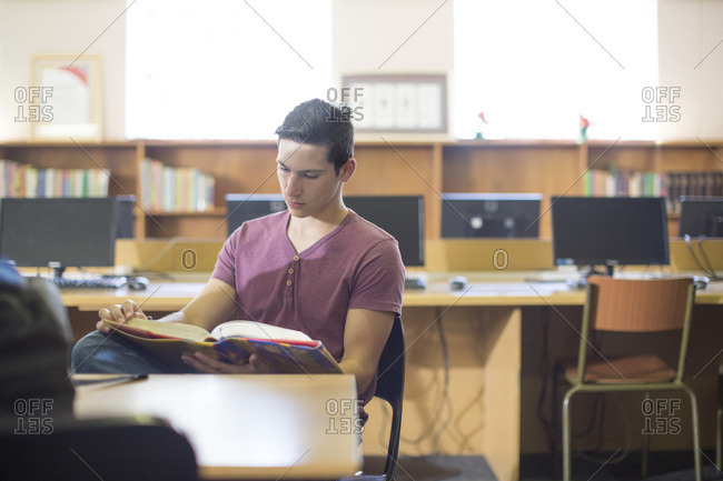 High school student reading a book