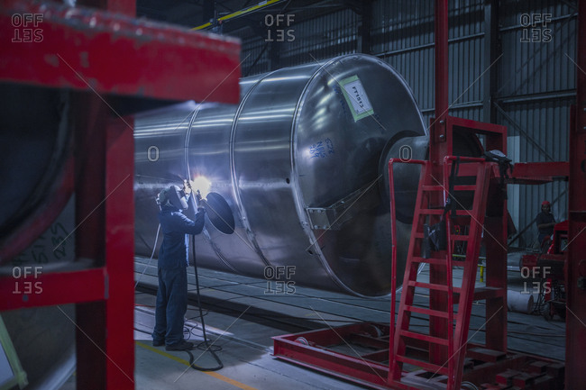 Man welding large steel tank in factory