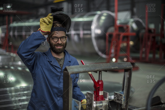 Portrait of smiling man wearing a welding mask in a factory