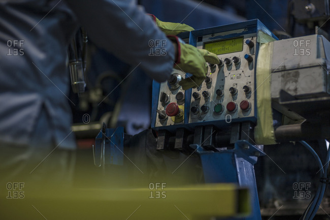 Worker operating machinery at control panel in factory