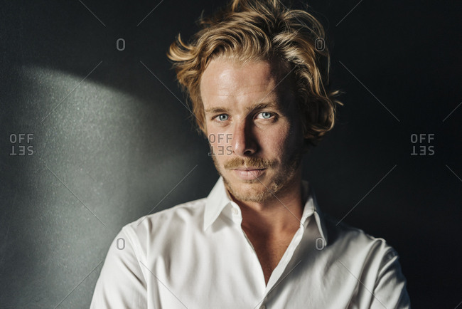 Portrait of confident blond man wearing white shirt