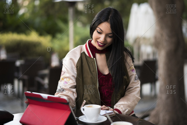 Young woman in bar terrace with notebook and tablet drinking coffee