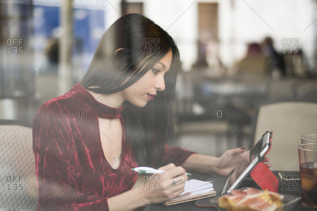 Woman in bar terrace looking tablet and writing in notebook