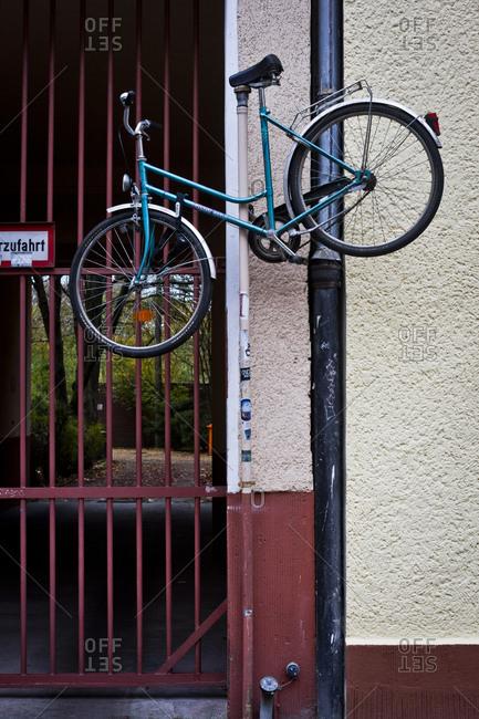A bicycle hung halfway up a lampost