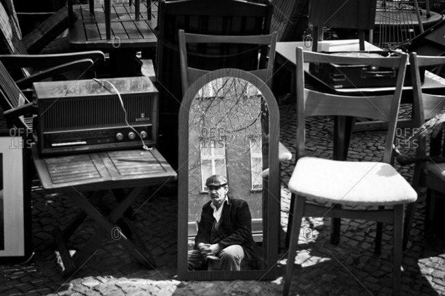 A vendor at a furniture stall in a flea market is reflected in a mirror