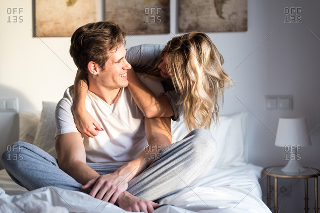 Happy young couple relaxed at home on bed