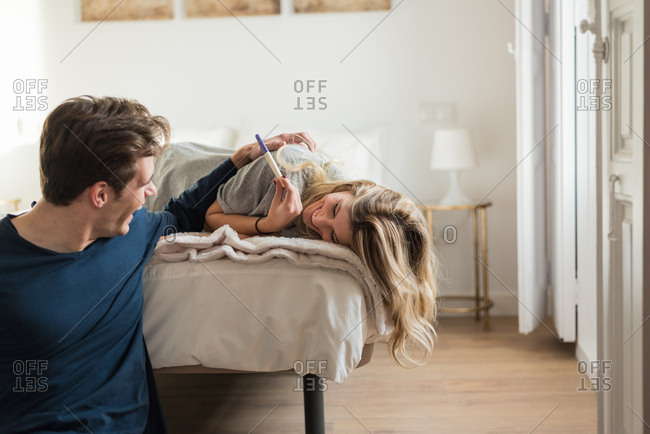 Happy young couple looking at pregnancy test on bed